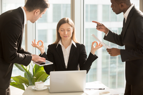 woman meditating around coworkers