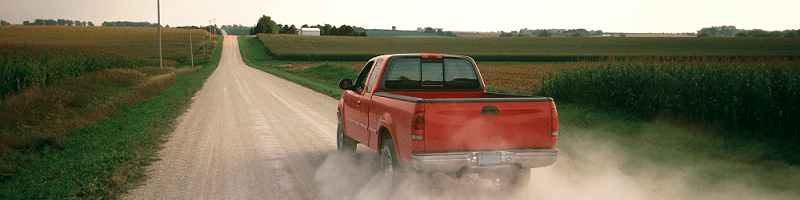 red pickup truck driving down a country road kicking up dust
