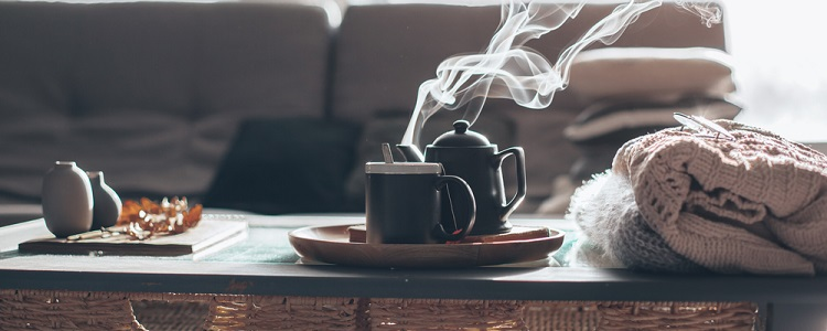 tea set on a coffee table beside a stack of sweaters